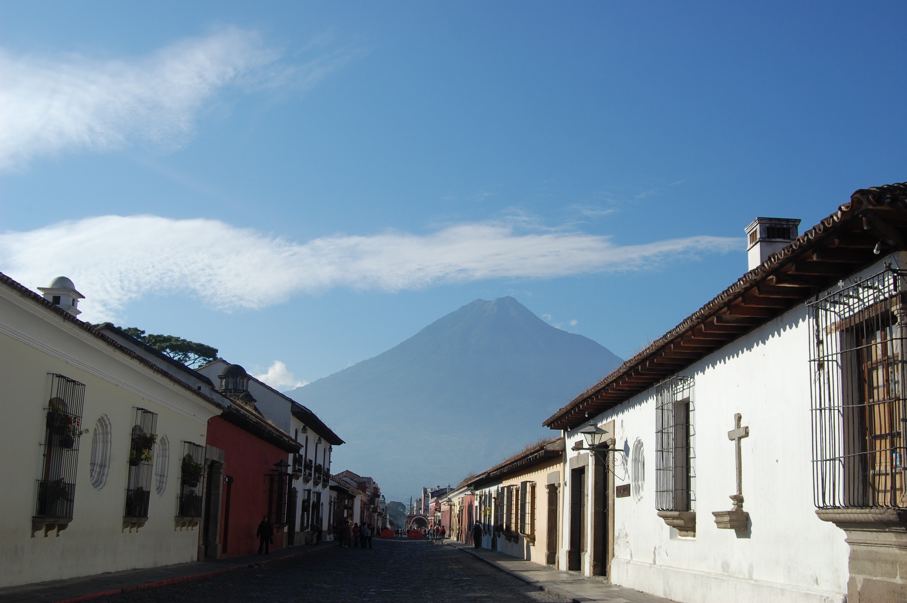 Street with beautiful Spanish colonial architecture and volcano looming in the distance.
